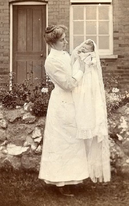 Edwardian nurse poses with a new baby.
