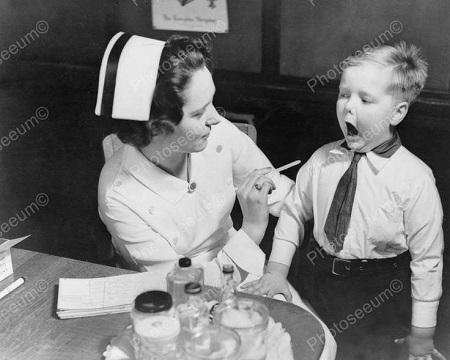Nurse asking a young patient to open his mouth.